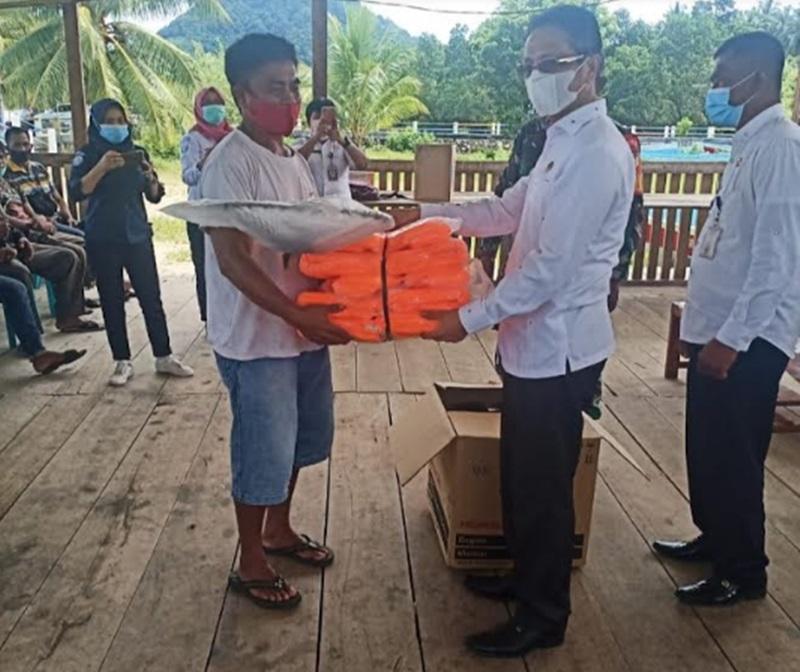 Wabup Bolmong saat menyerahkan paket bantuan perikanan tangkap, bagi kelompok nelayan di Desa Maelang, Kecamatan Sangtongbolang.